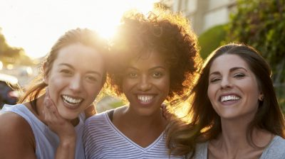 Portrait of three young adult female friends in the street