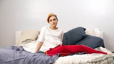 A trans young person sitting on a bed
