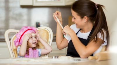 Happy mother and little girl making fun with dough