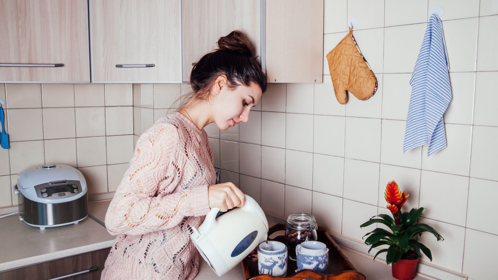 Young woman preparing tea in the kitchen. Pouring water into a cup.