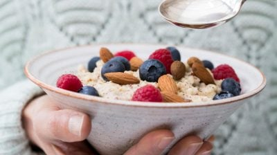Close Up Of Woman Eating Bowl Of Porridge with Fruit And Nuts For Healthy Breakfast