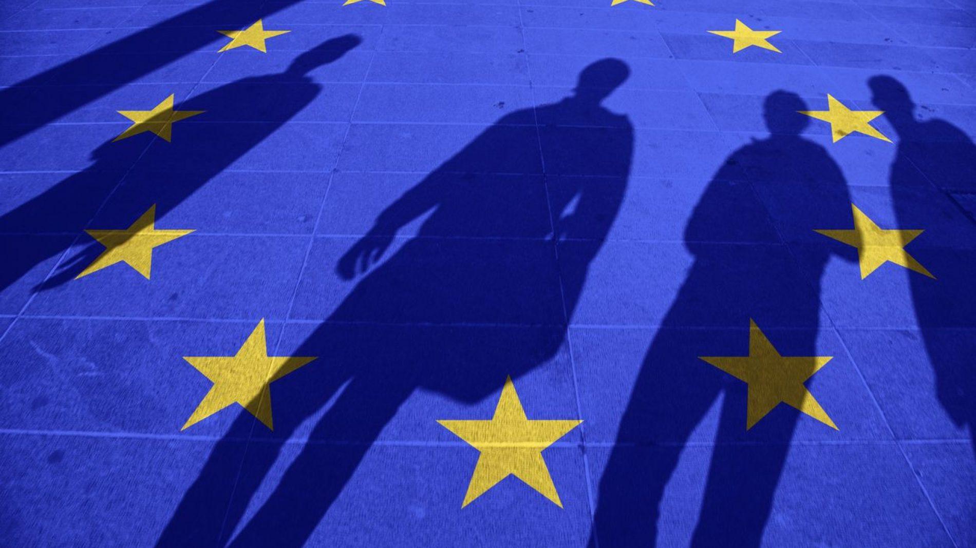 Shadows standing over the EU flag