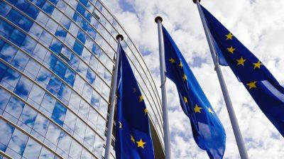 Three European Union flags outside the European Parliament building
