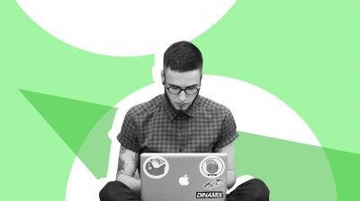 Young man on his laptop in front of a green and white background