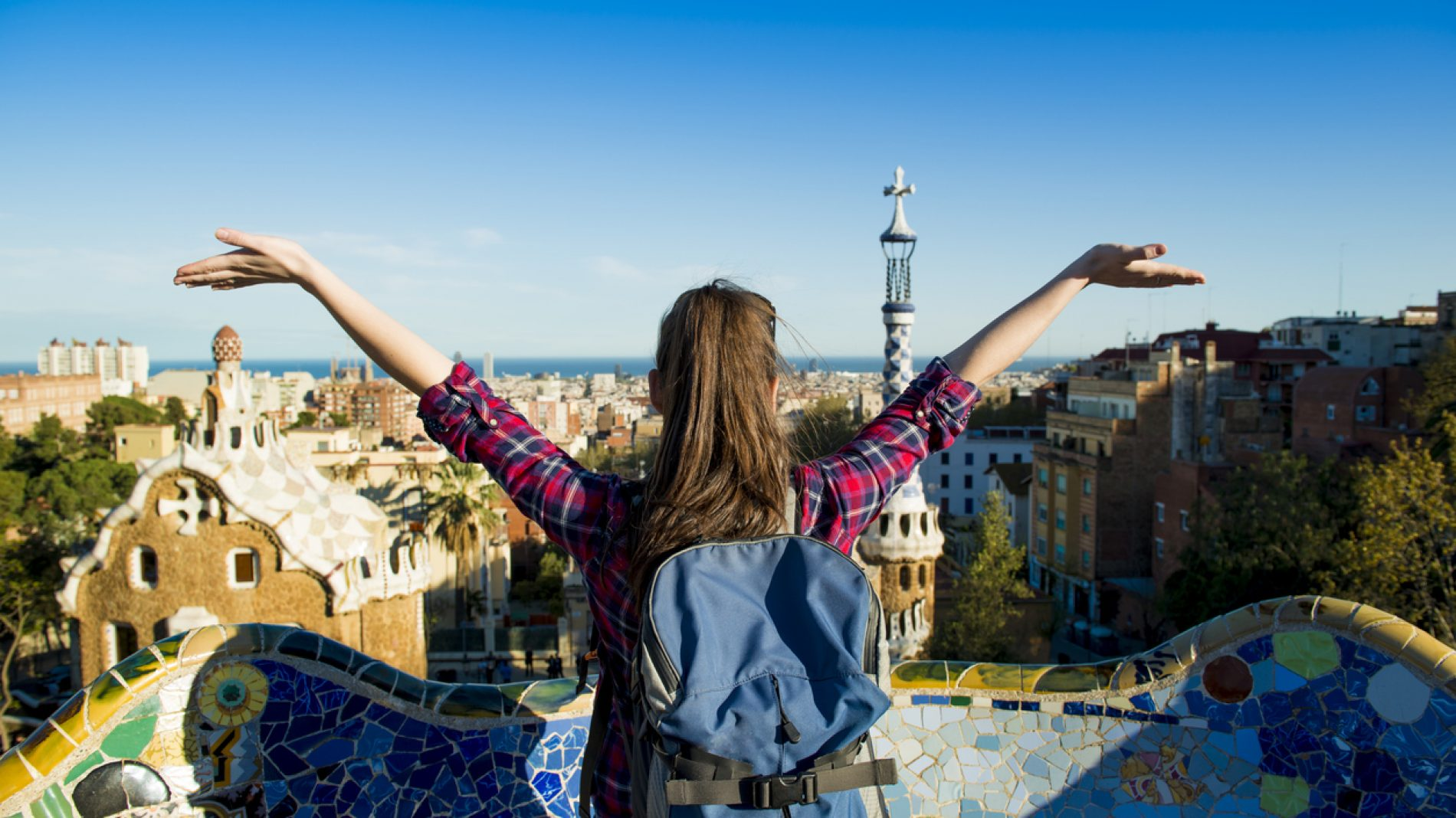 Girl looking over a city with her arms in the air