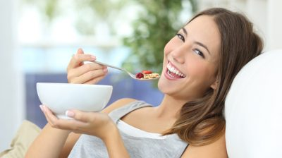 Happy girl eating cereals at home