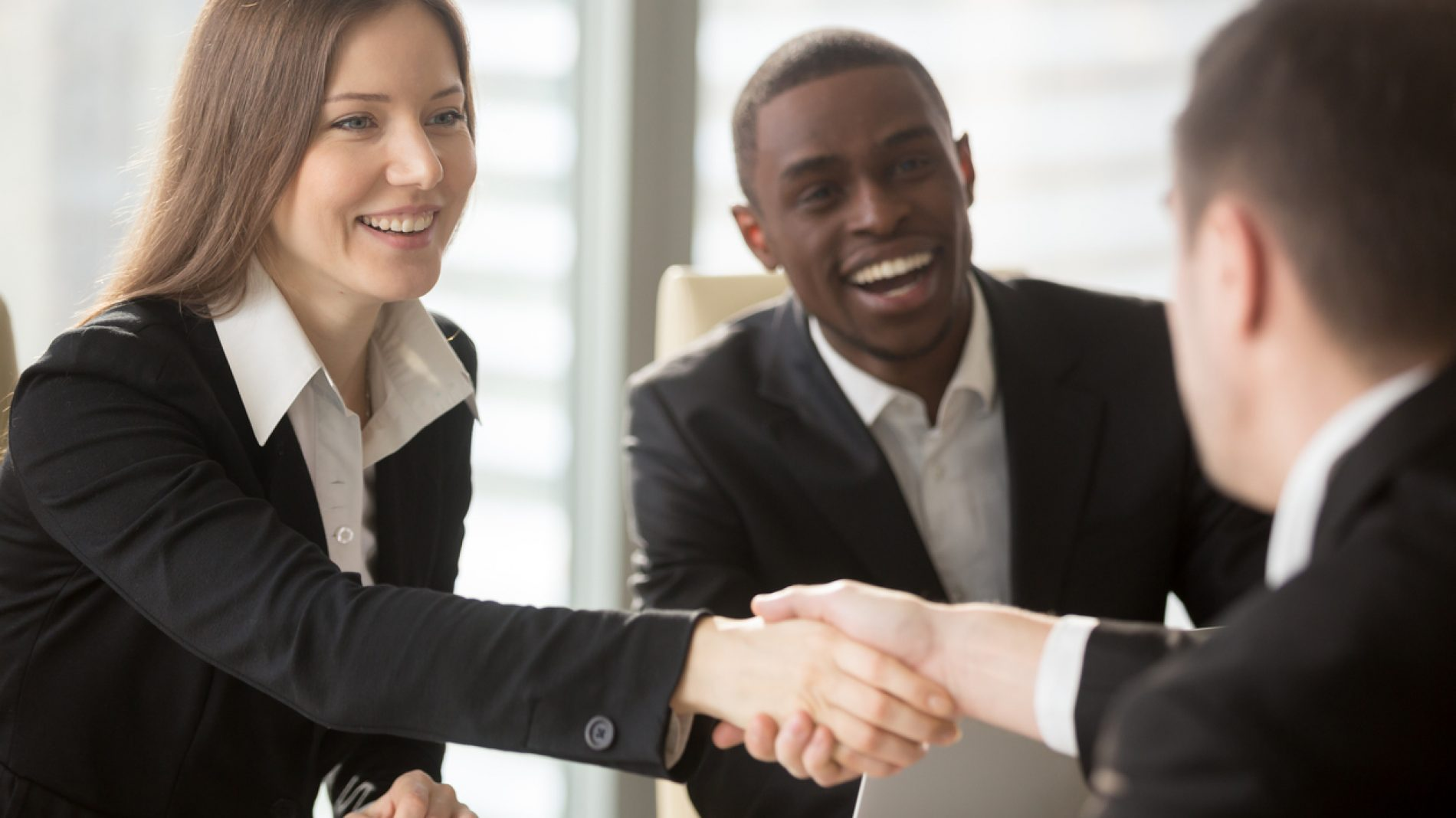 Female HR manager handshaking with job applicant