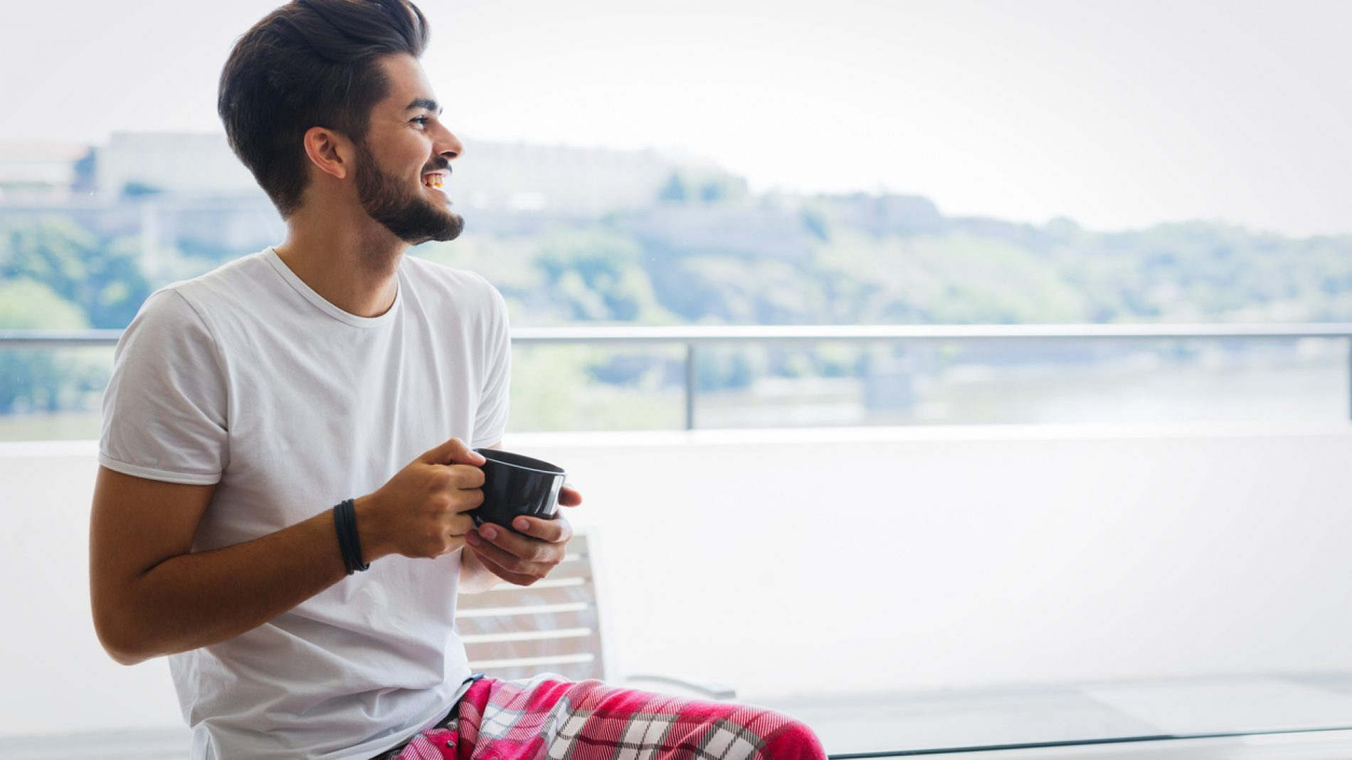 Man sitting with tea and smiling