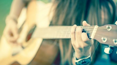 closeup of female's hands playing acoustic guitar with vintage tone