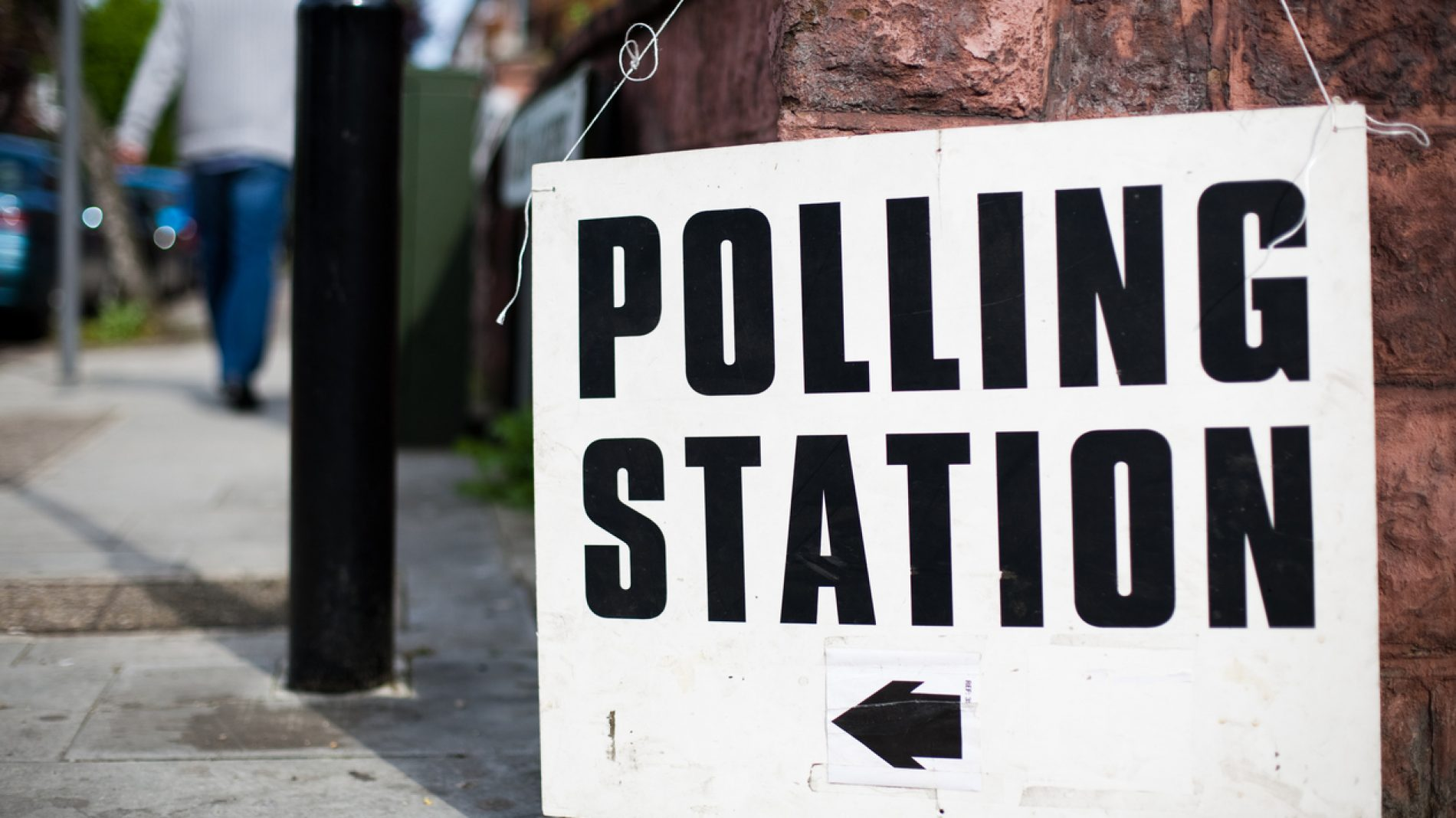 A uk Polling station sign hooked on a wall on a street