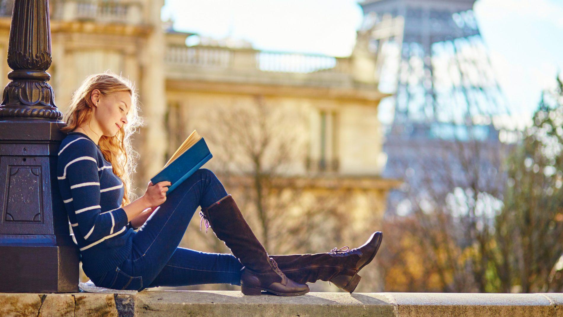 Beautiful woman in Paris, reading a book