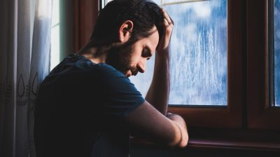 Man leaning against a window looking sad