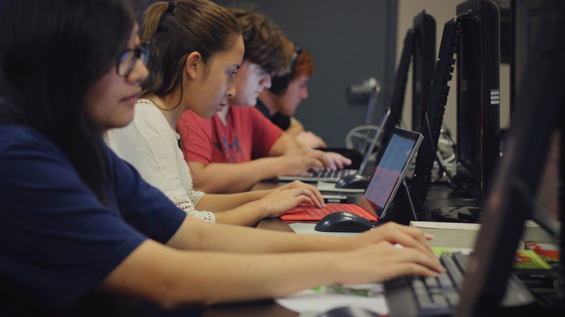School students studying together in a computer lab