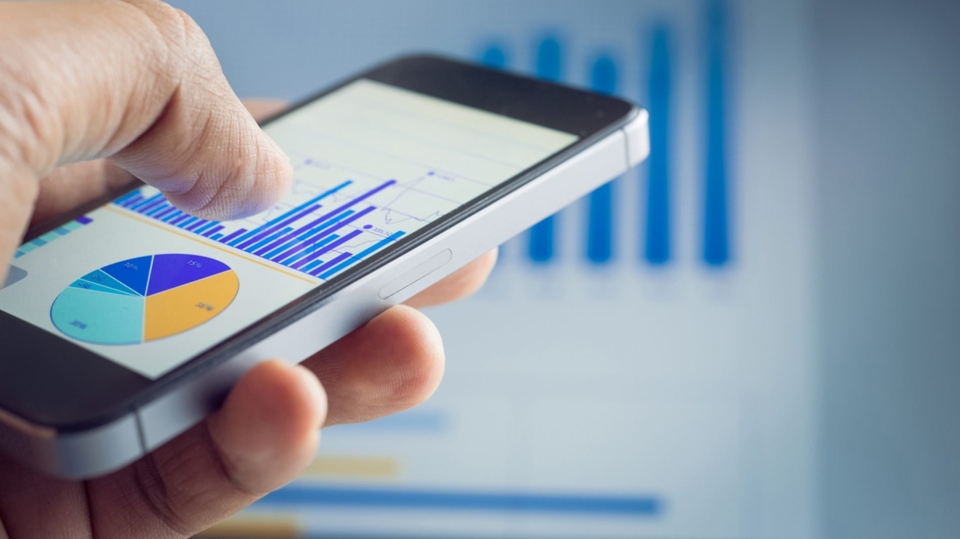 Businessman hand holding smartphone with graph chart on laptop background.For business market  concept