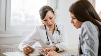 Charming female doctor giving advice to a female patient.