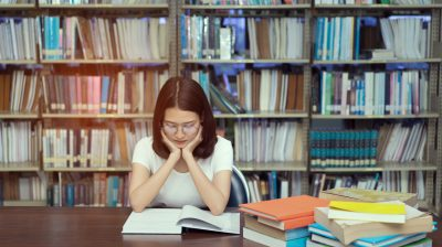 Young student asian girl with glasses reading book serious vision eyesight Hard exam, test and tired stress headache alert worry in classroom library high school university campus college and knowledge center.
