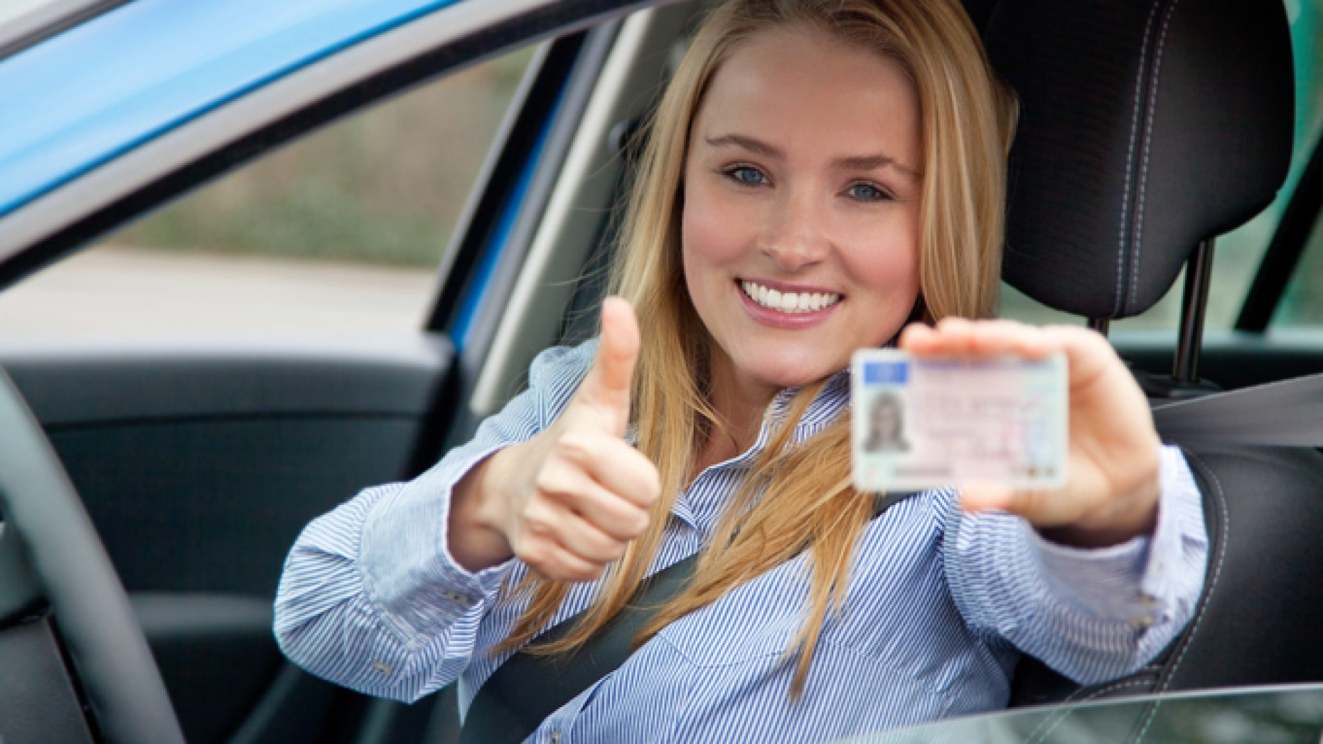 Women holding driving licence in car