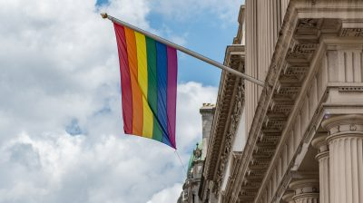 a pride flag hanging from a building