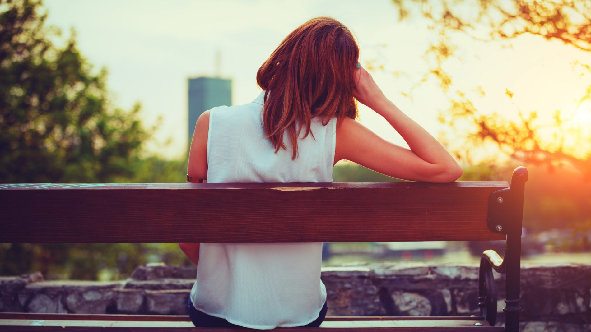Girl enjoying city view from a bench.