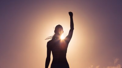 a woman reaching her hand towards the sky