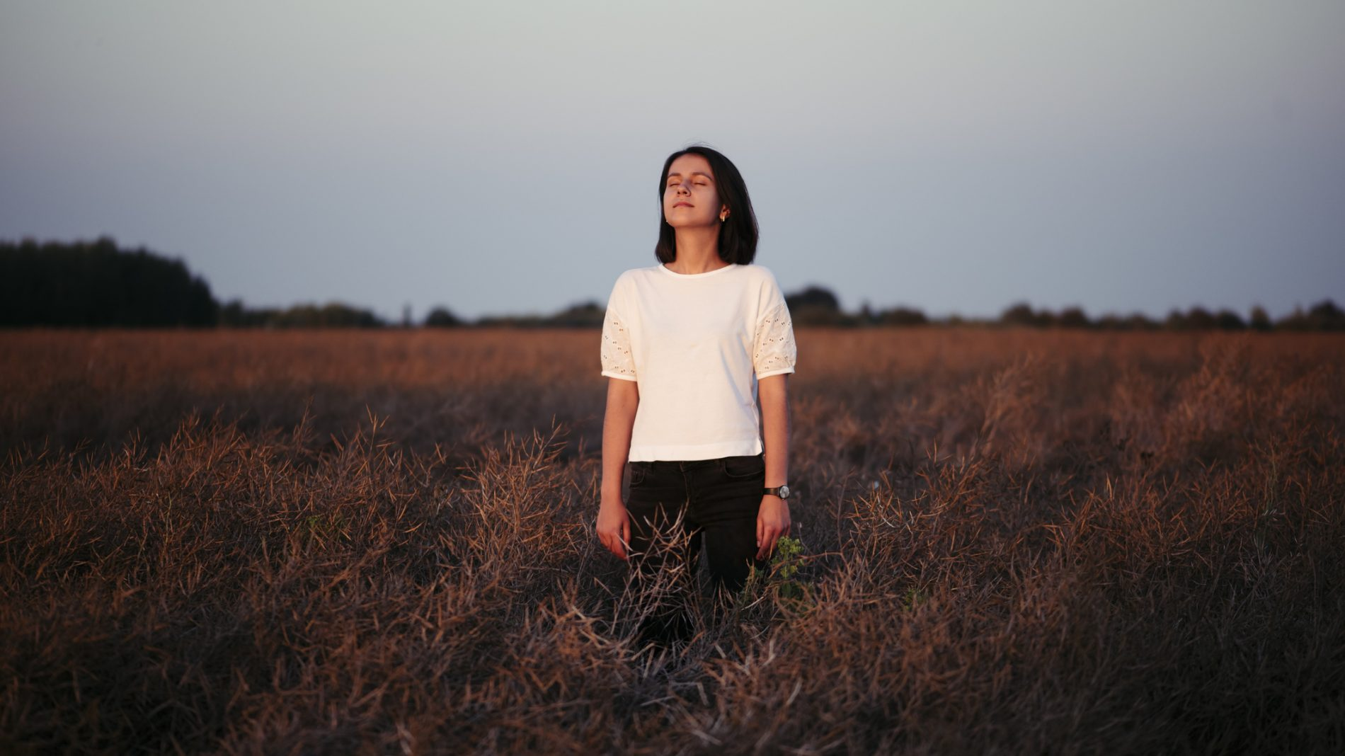 Woman standing alone in the sunset field, enjoying solitude