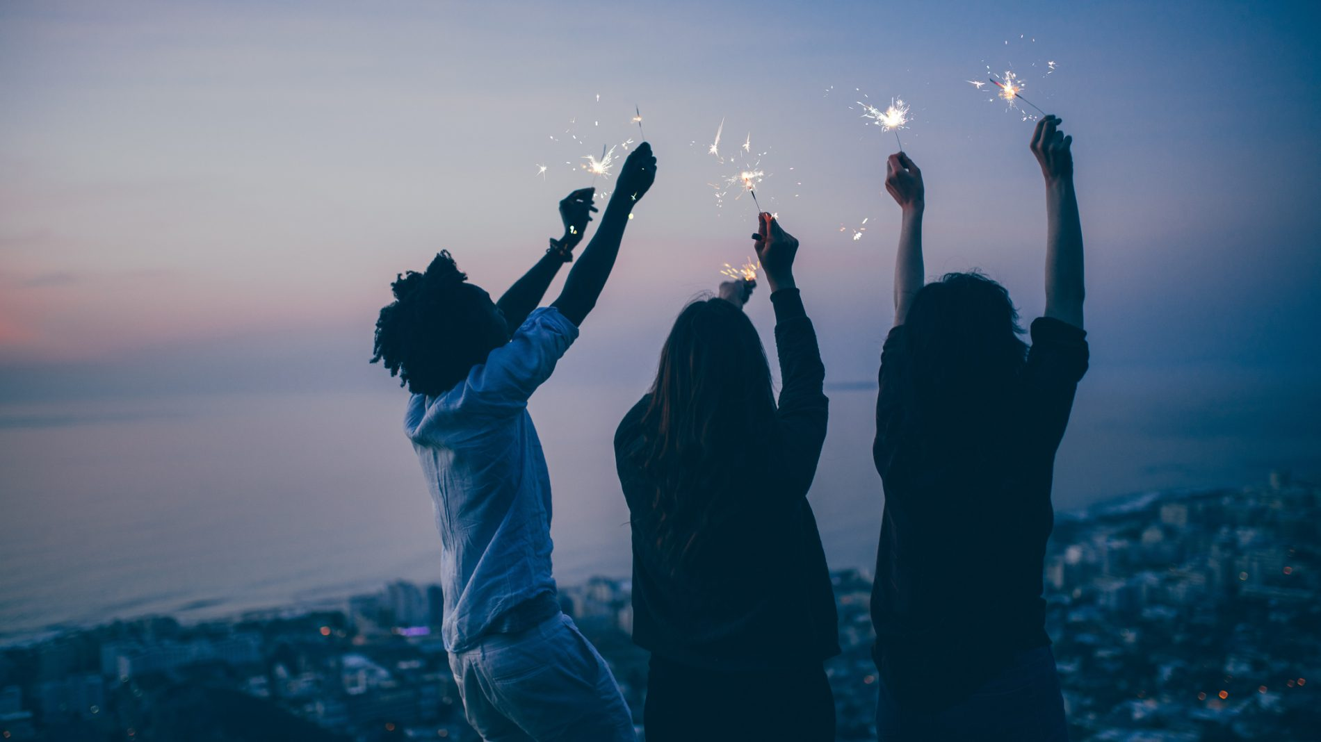 Group of young adult friends celebrate with sparklers at night