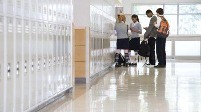 School children by lockers in corridor