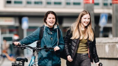 Two-college-students-walking-with-a-bike-3zE2AM
