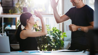 Two people high fiving in work