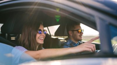Two-young-people-driving-and-smiling-IokGEe
