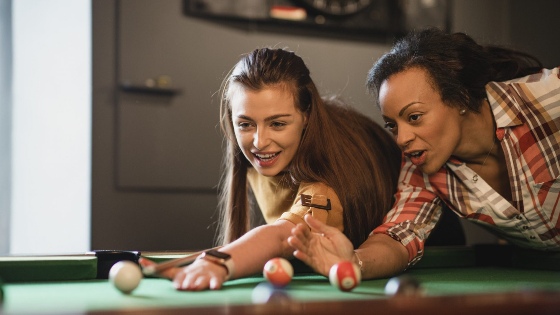 Two young people playing pool in a pub