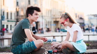 Two-young-people-sitting-on-a-bridge-together