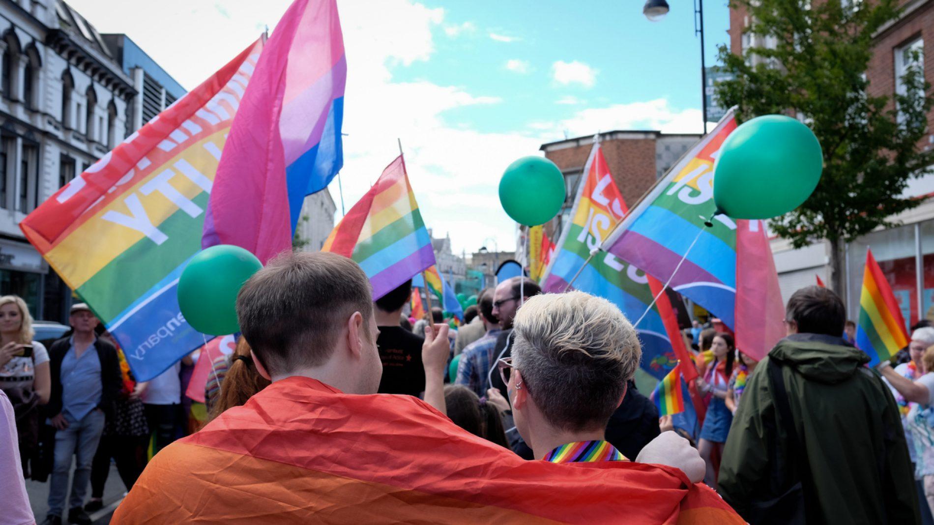 Two people walking through Pride