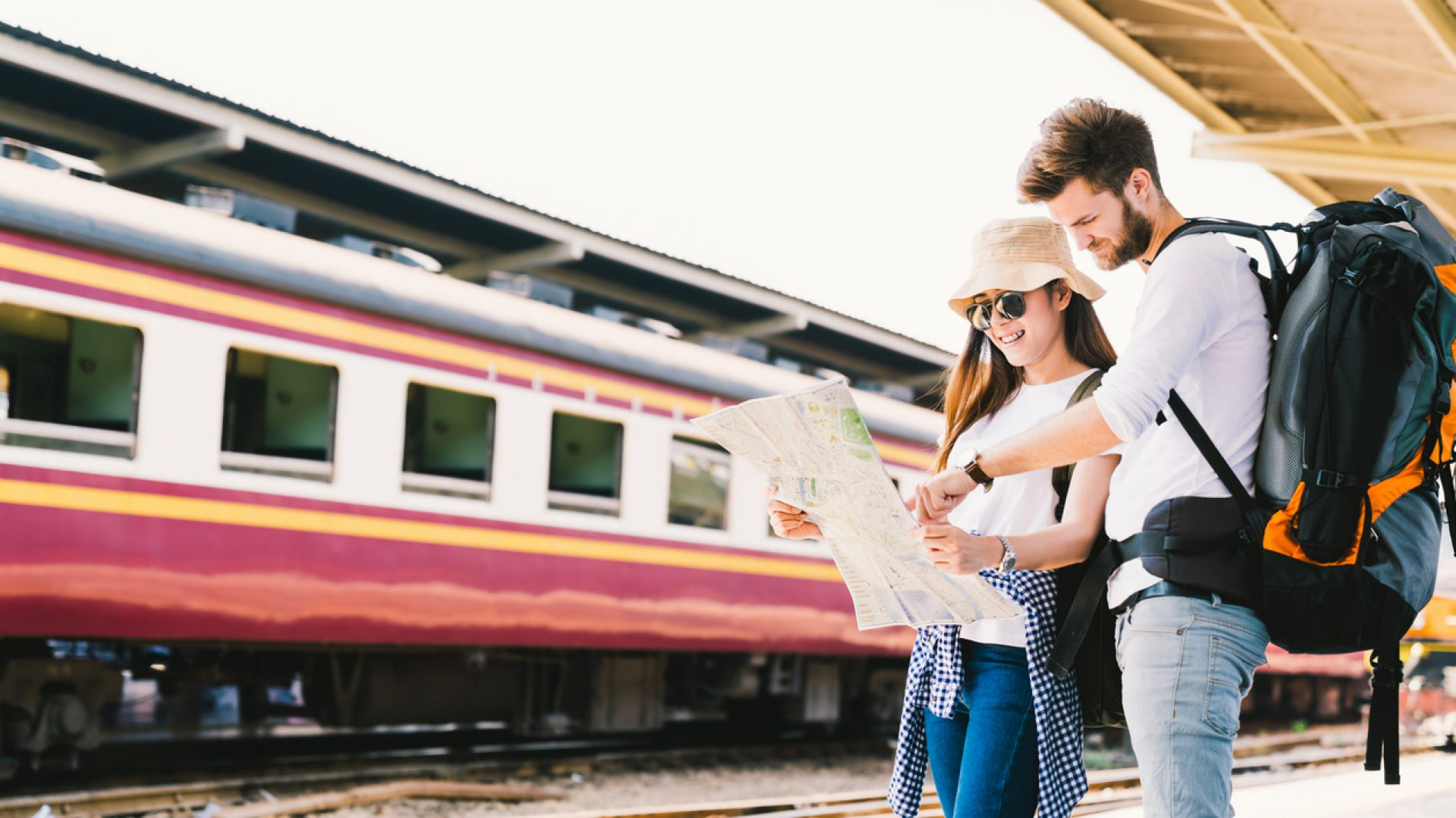 Two people in a train station looking at a map