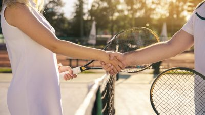 Male and female tennis players shaking hands on net