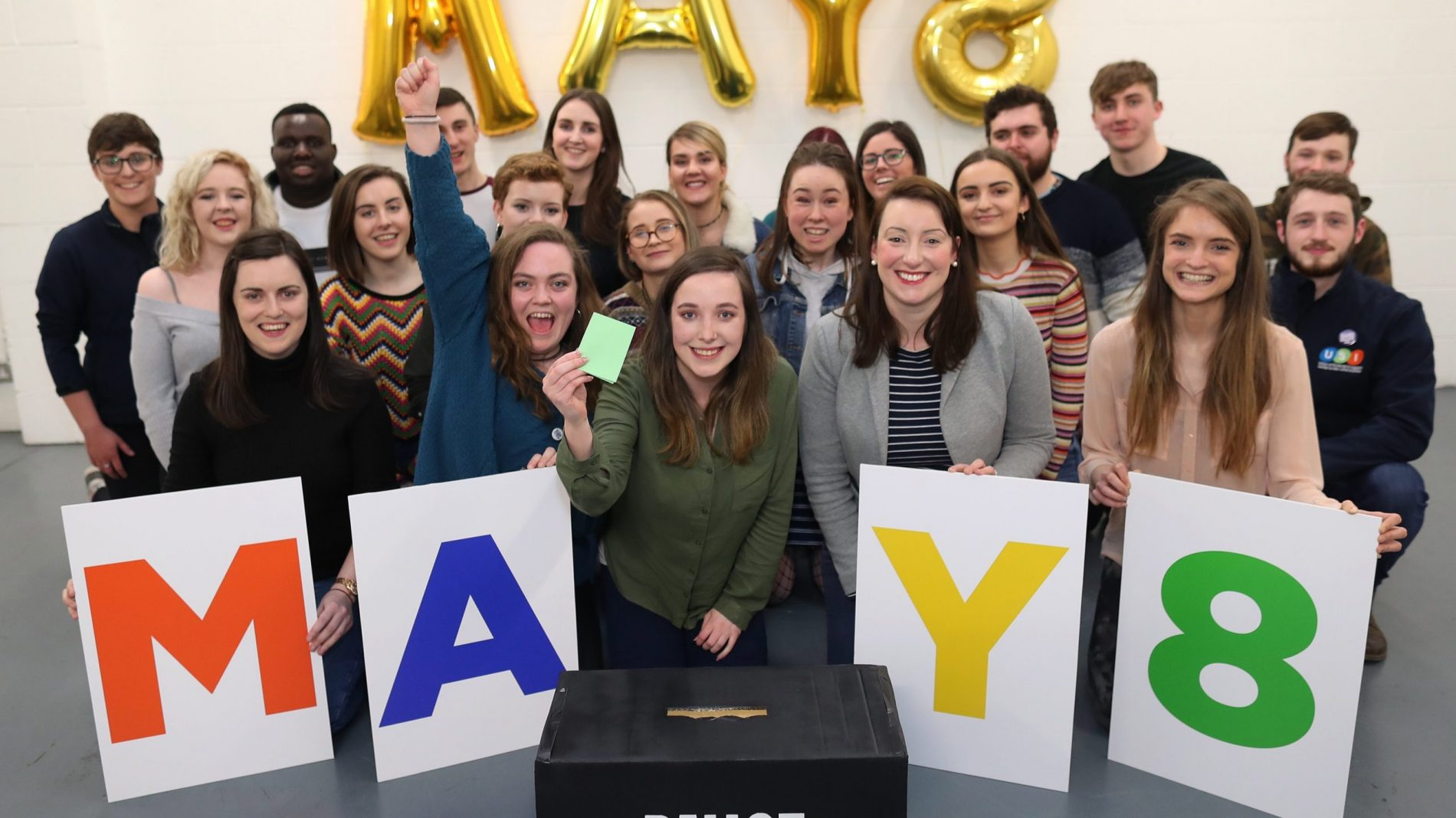 Young people with May 8 signs, in front of a ballot box