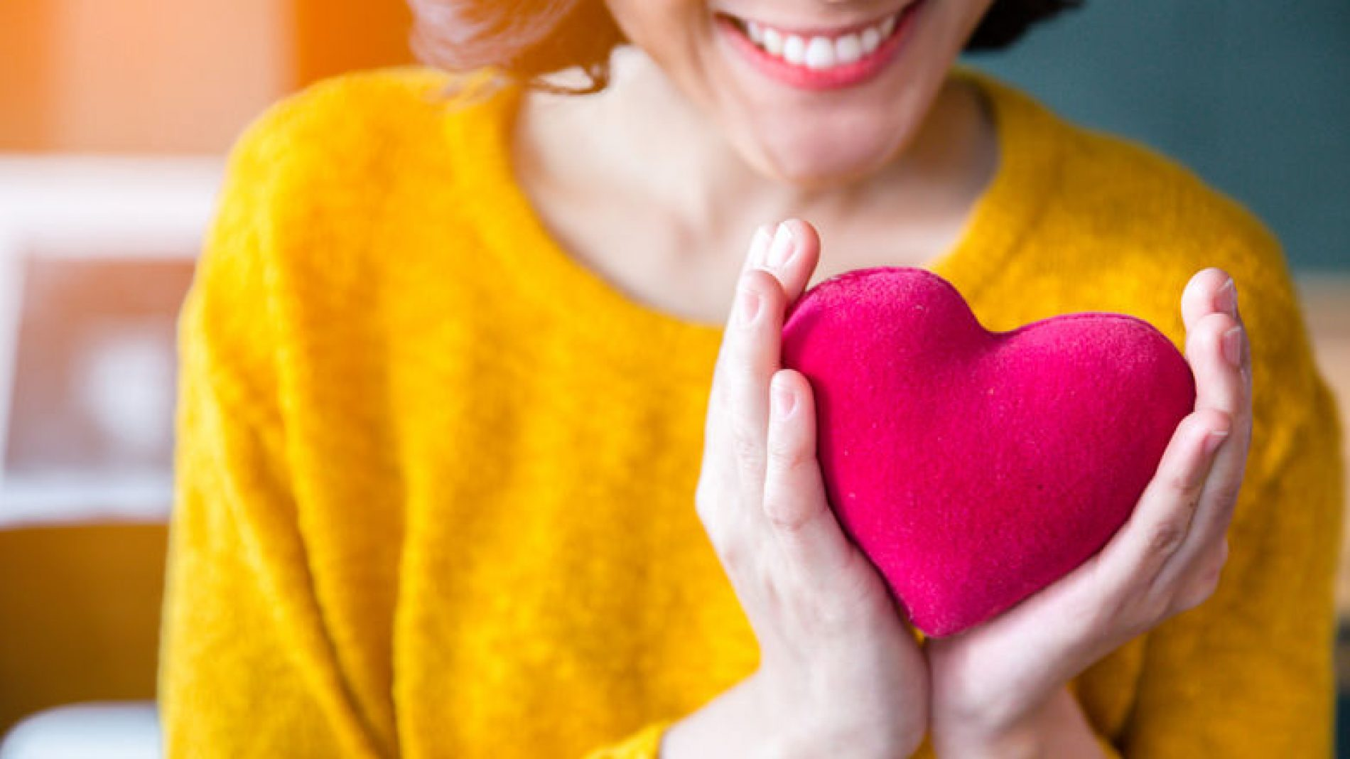 Woman-smiling-and-holding-toy-heart