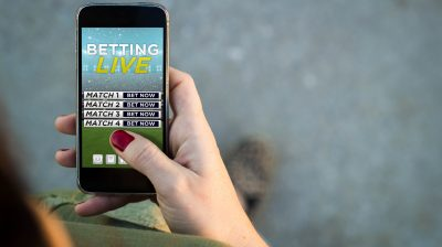Woman walking smartphone bet online interface
