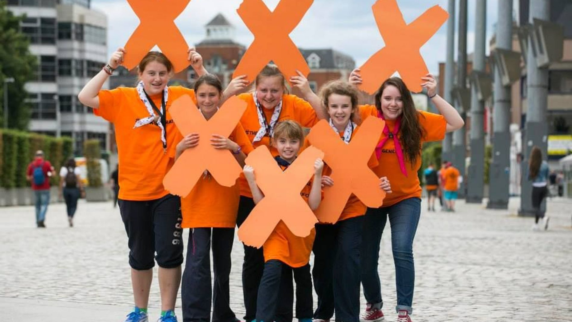 group of young people holding up x's
