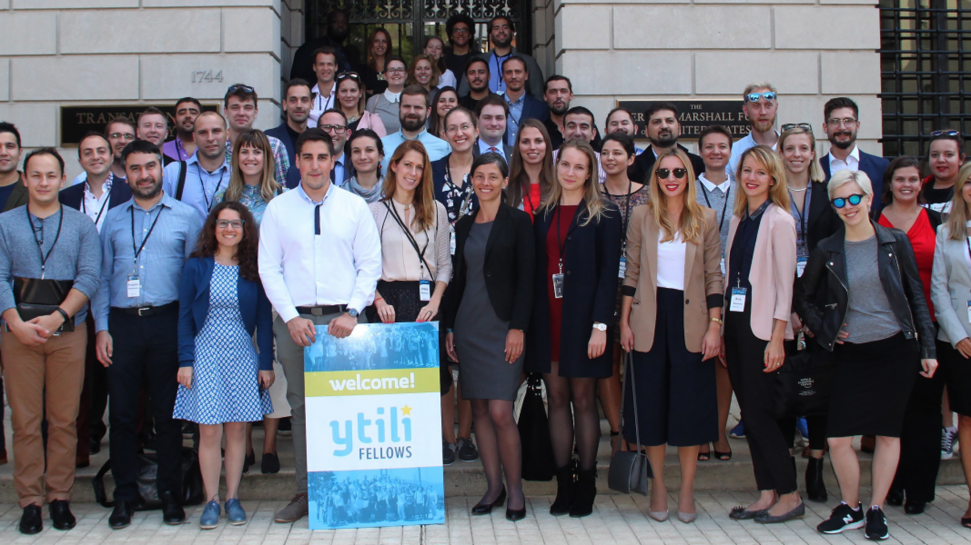 Fellows from the YTILI standing together on steps of a building.