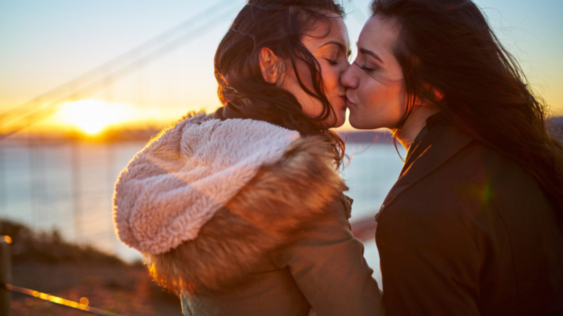 Young-couple-kissing-in-front-of-a-bridge-7zpktI