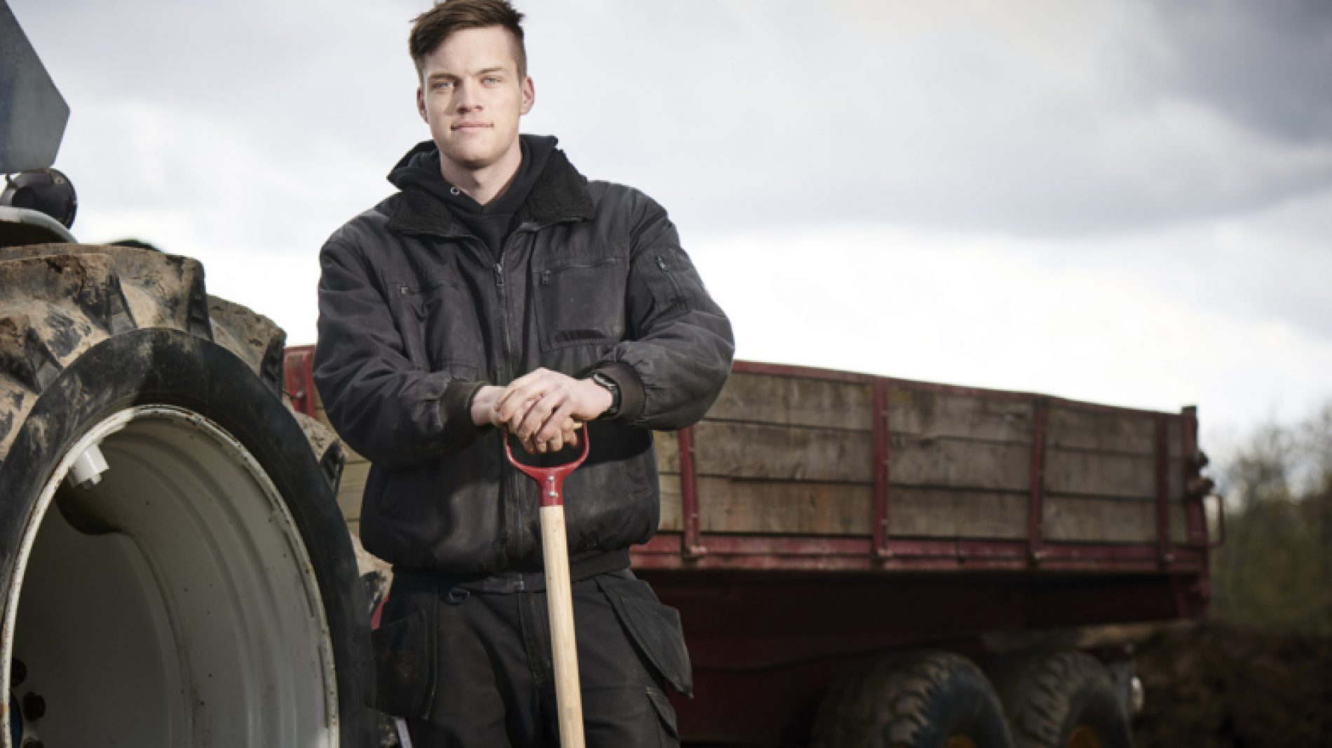Young-farmer-standing-infront-of-a-tractor-HoEKkq