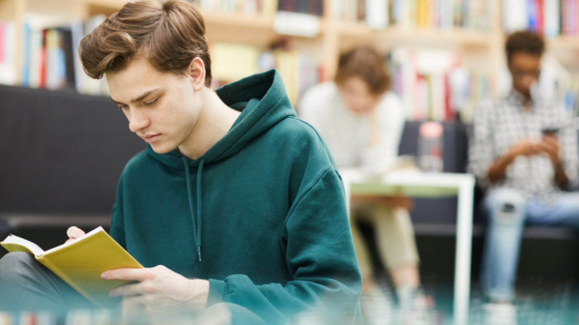 Young-man-in-the-library-reading-QsjhLz