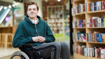 Young-man-in-wheelchair-in-the-school-library-5FBdWP