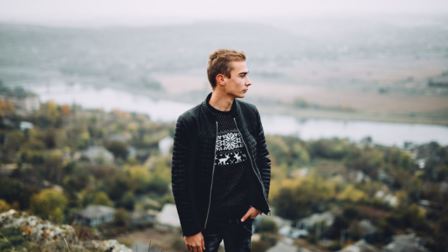 Young-man-on-a-hill-looking-at-the-view-CjFlfZ