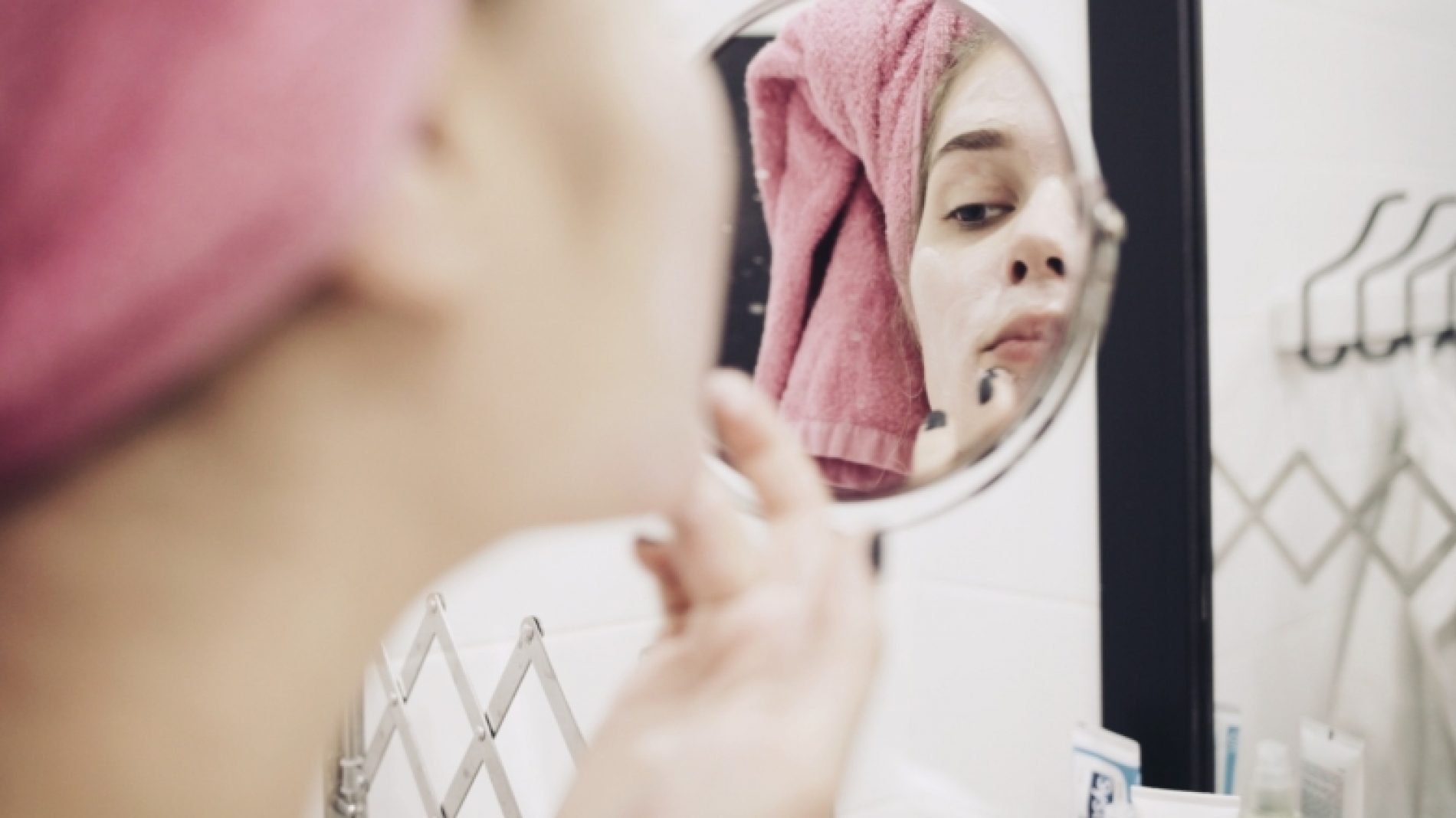 Young-person-cleaning-their-face-in-the-mirror-jfq16q