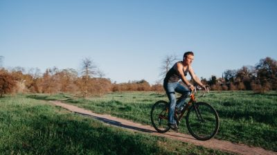 Young-person-cycling-on-their-bike-through-a-field-AsPtOq