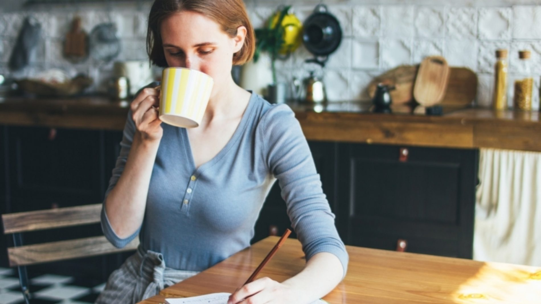 Young-person-journaling-and-drinking-tea-bcAQvd