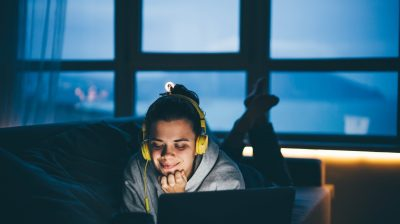Young person listening to a podcast at night