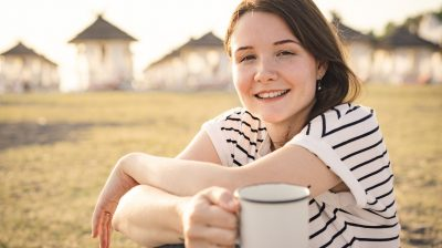 Young person sitting outside with tea